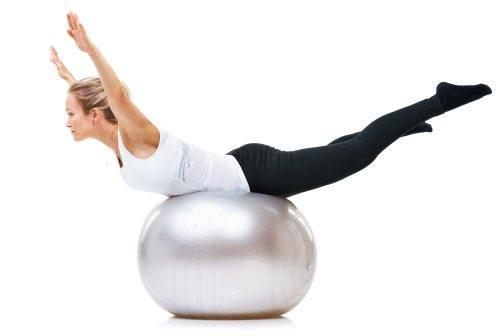 Kvinde holder balancen på en Pilates bold